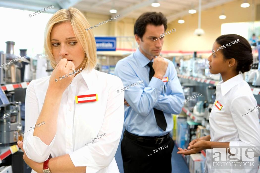 Stock Photo: Young saleswoman with hand to face, colleagues in conversation in background.