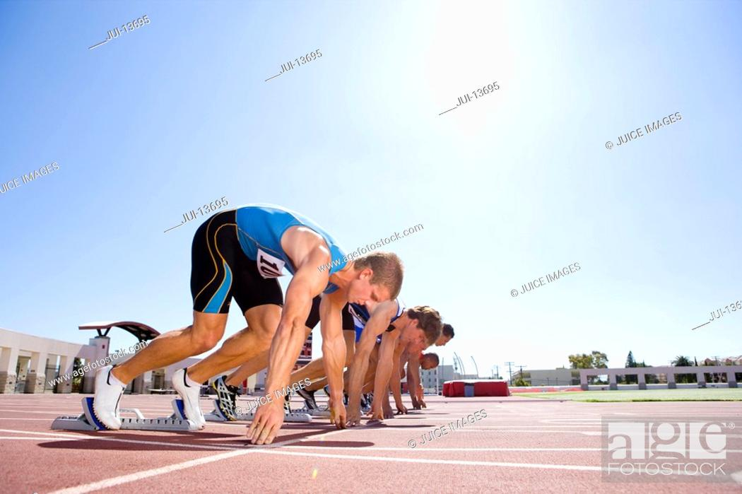 Stock Photo: Male sprinters on starting blocks, low angle view sun flare.