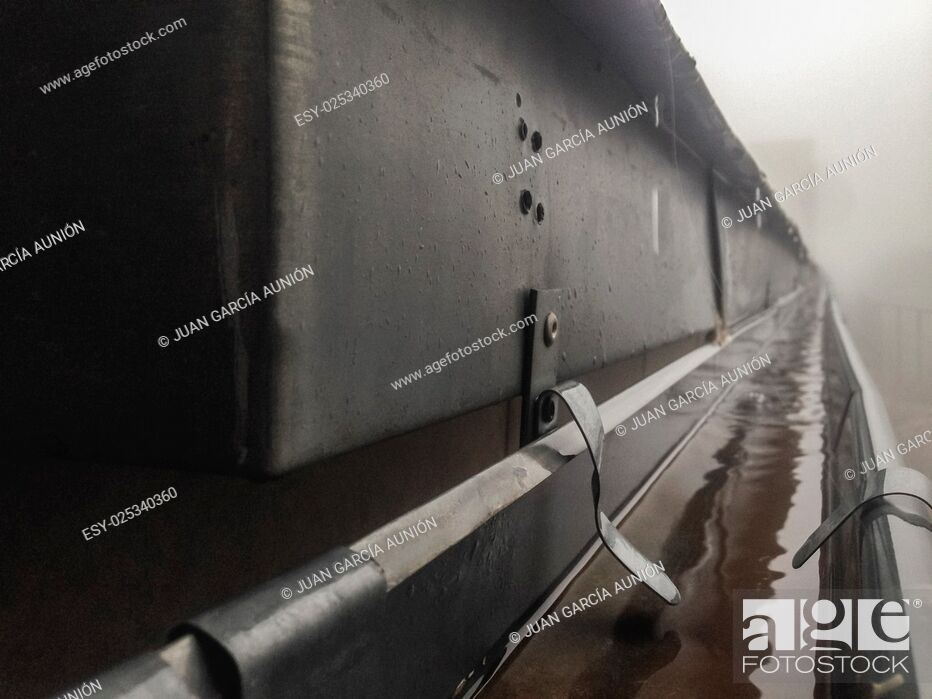 Stock Photo: Gutter drainage system on the roof with dripping fog and rain. Closeup.