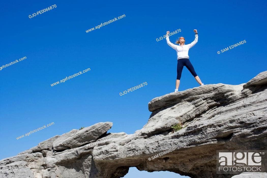 Stock Photo: Woman standing on rock bridge.