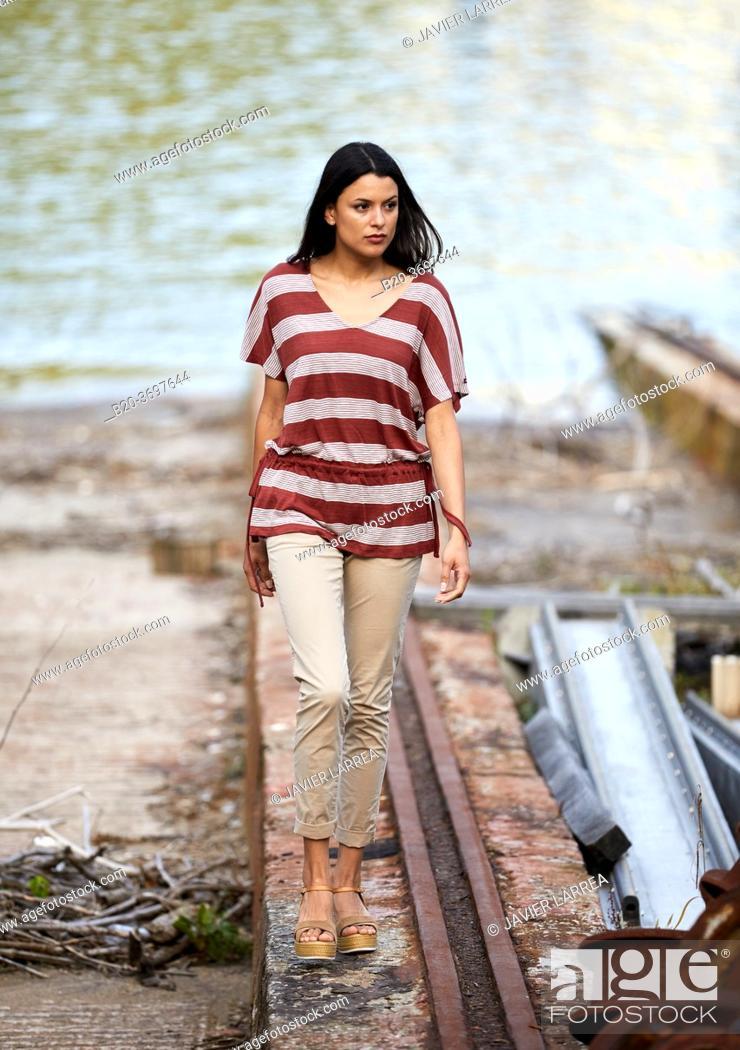 Stock Photo: Young woman walking in shipyard, ship in the port of Pasaia, Gipuzkoa, Basque Country, Spain, Europe.