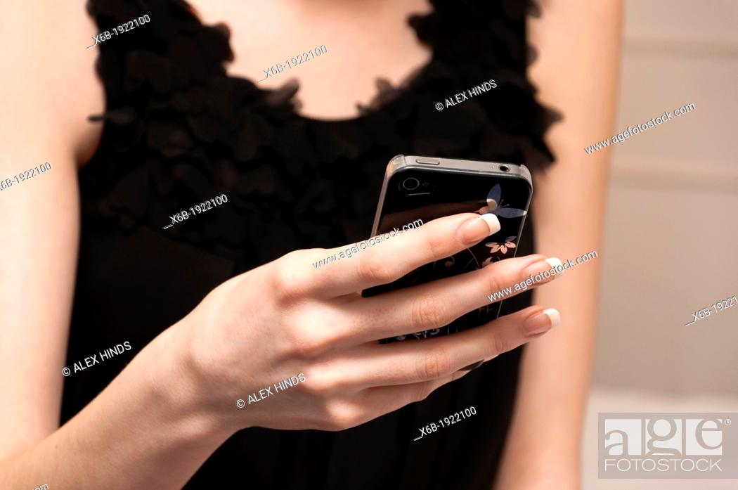 Stock Photo: Pretty girl in little black dress texting on mobile phone.