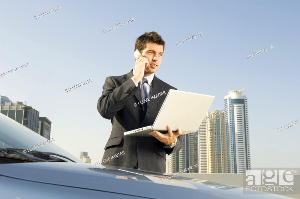 Stock Photo: A businessman talkingon a mobile phone holding a laptop.