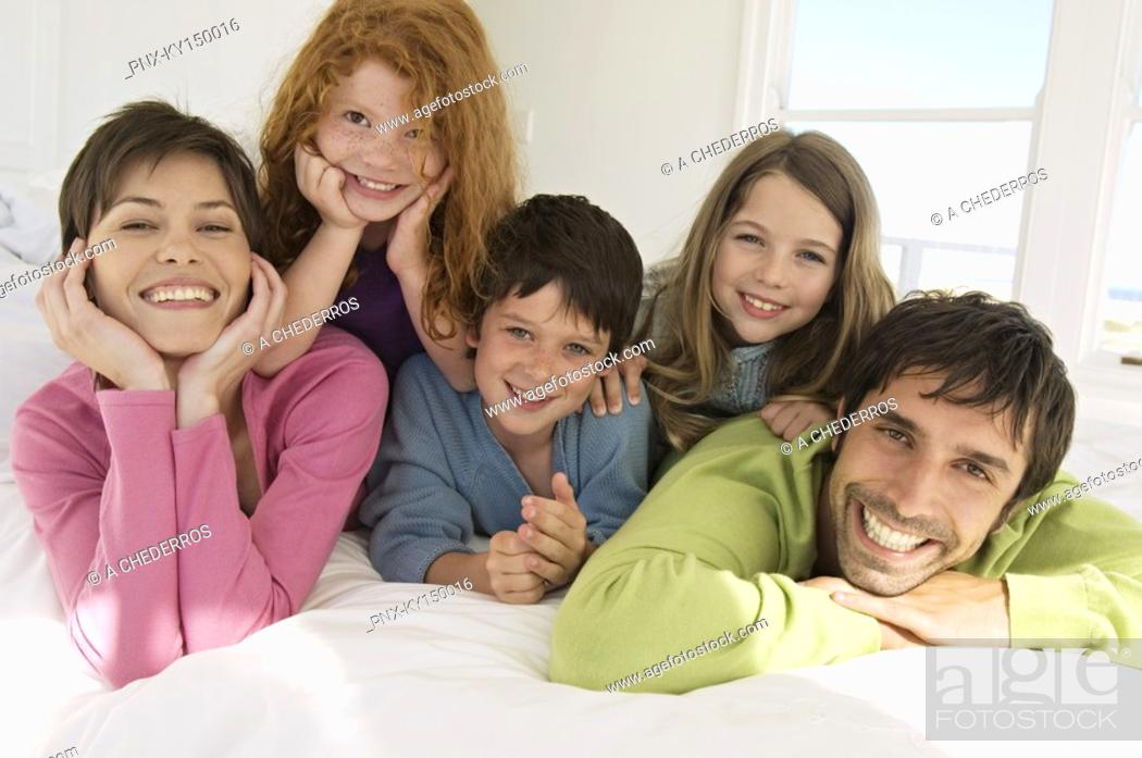Stock Photo: Smiling couple with 3 children lying on bed.