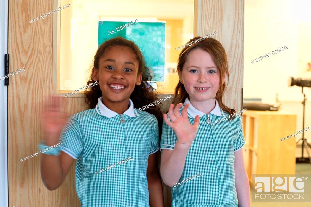 Stock Photo: Portrait of two schoolgirls waving in primary school.