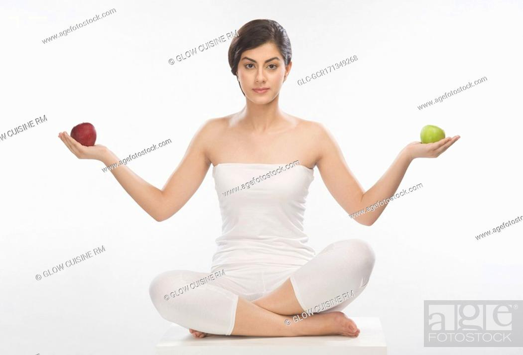 Stock Photo: Portrait of a woman holding a red and a green apple.