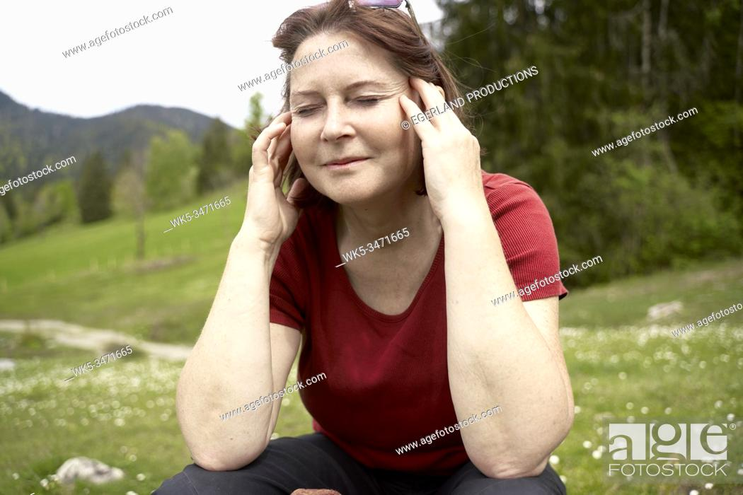 Imagen: Mature woman in countryside with eyes closed. Bad Tölz, Upper bavaria, Germany.