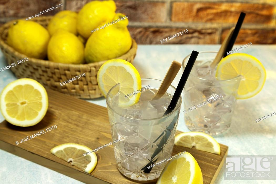Stock Photo: two glasses of lemonade with ice, spoon and straw on cutting board, cut lemons and basket with lemons on red brick bacground.