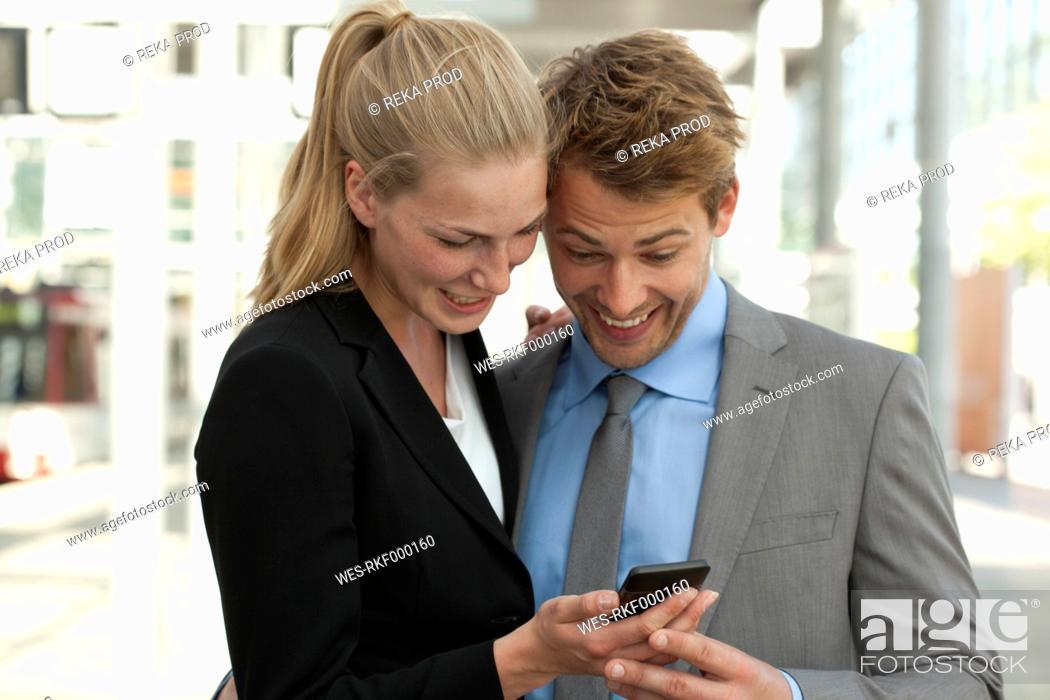 Stock Photo: Germany, North Rhine Westphalia, Duesseldorf, Business people using smart phone at station, smiling.