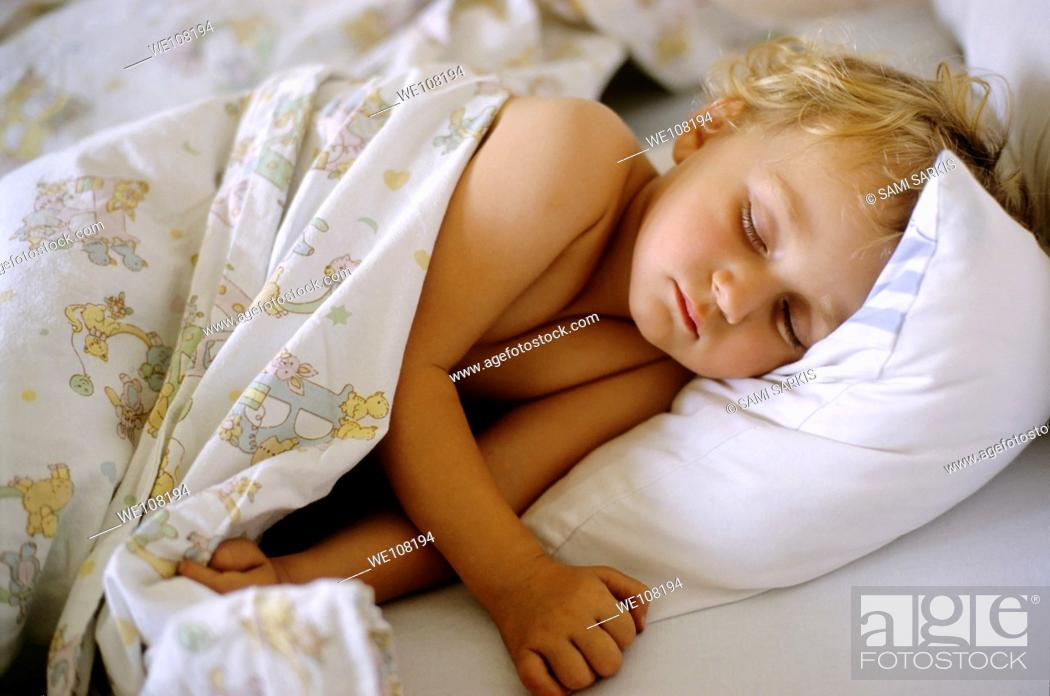 Stock Photo: Two year old girl asleep in bed, France.