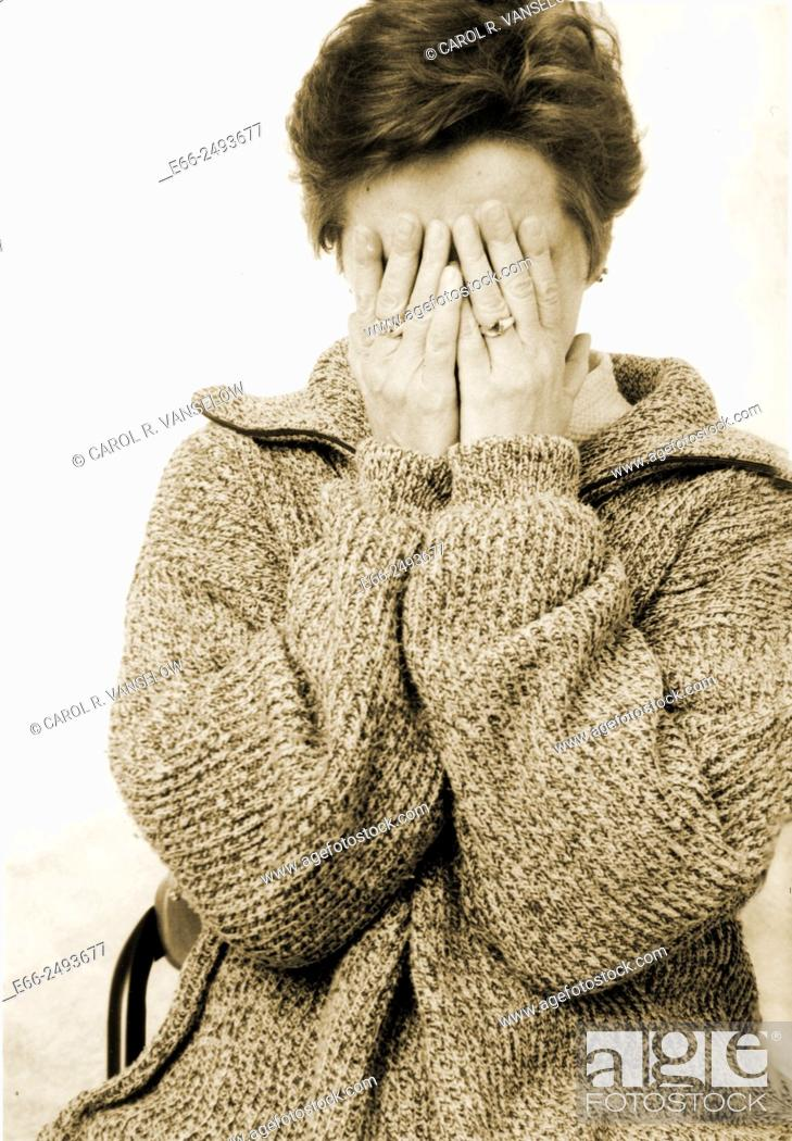 Stock Photo: Portrait of woman with hands covering face.