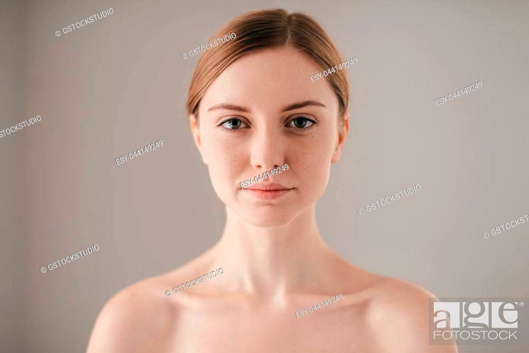 Stock Photo: Pure beauty. Portrait of redhead woman with freckles looking at camera while standing against grey background.