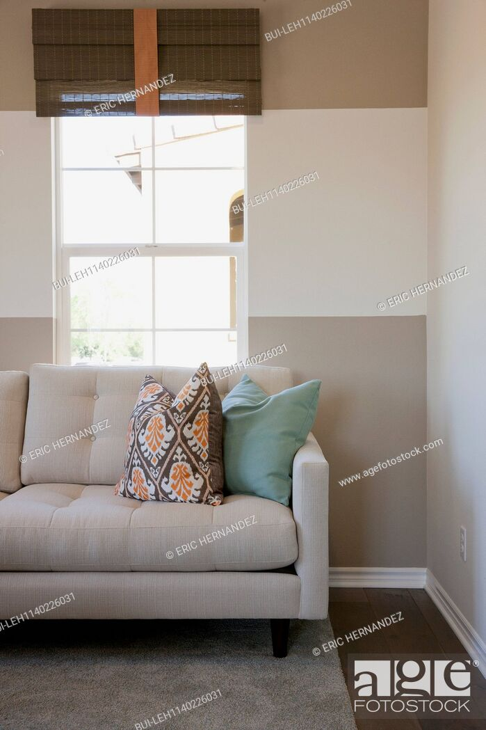 Imagen: Cushions on cropped couch against the window in the living room.