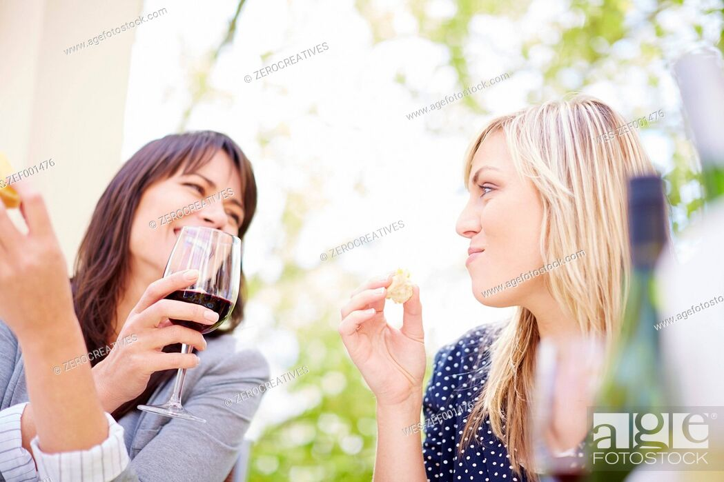 Stock Photo: Two happy women with red wine and white bread.