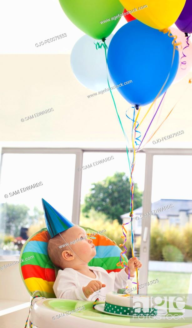 Stock Photo: Baby with birthday cake holding balloons.