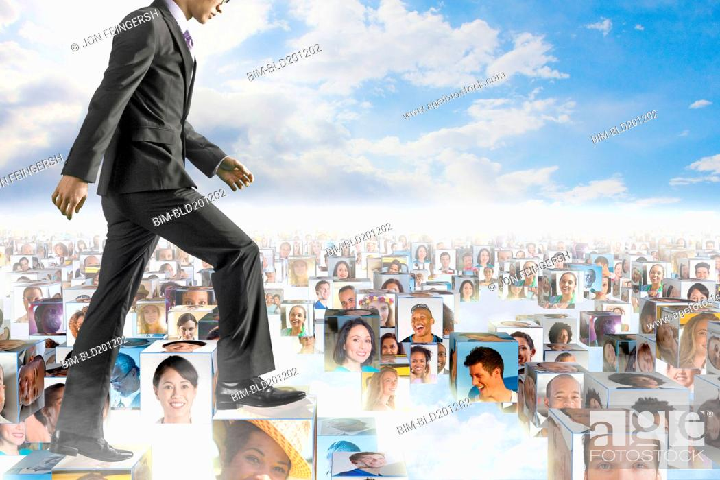 Stock Photo: Korean businessman walking over images of business people.