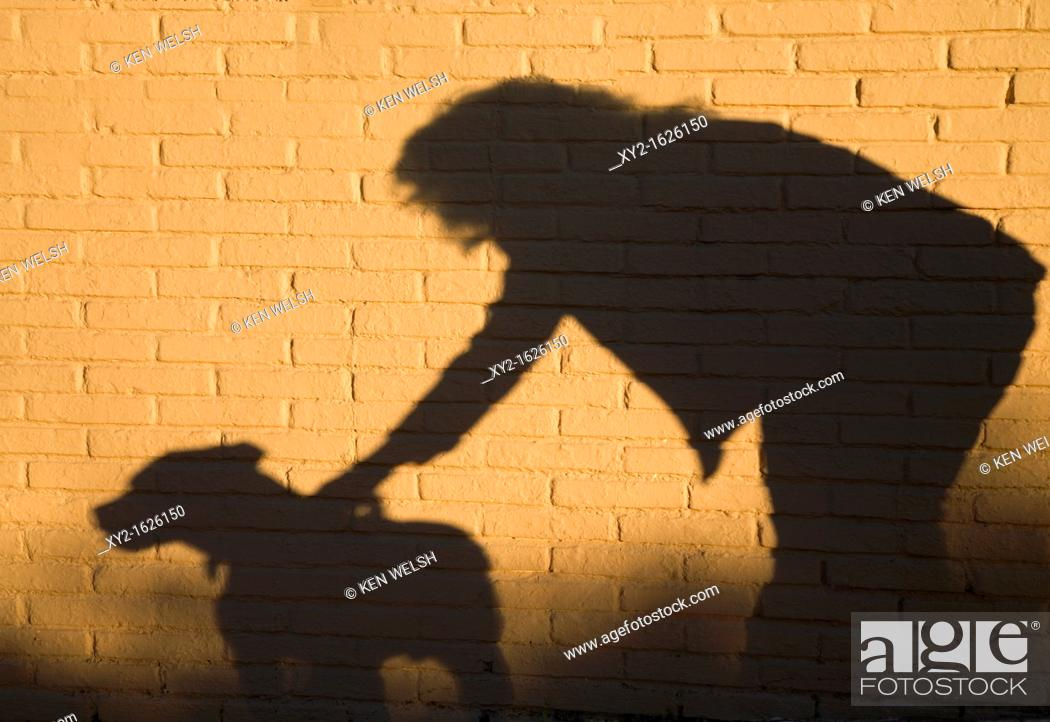 Stock Photo: Shadow of woman and dog against brick wall.