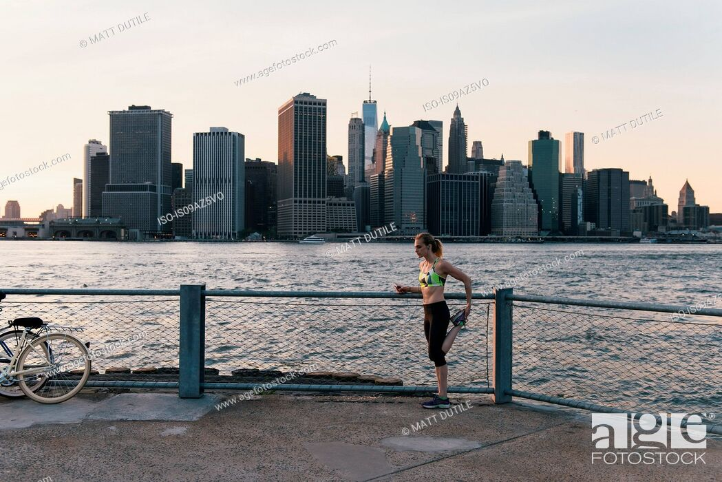 Stock Photo: Young woman exercising outdoors, stretching by waterfront, Brooklyn, New York, USA.