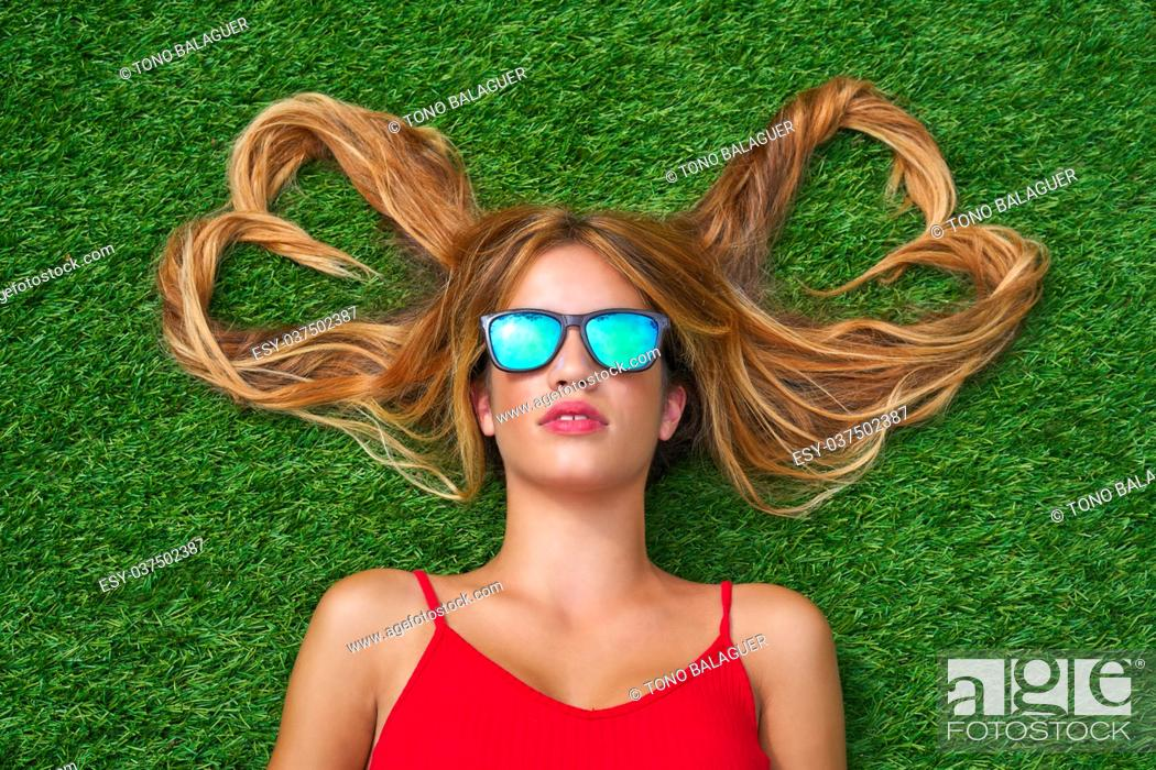 Imagen: Blond teen girl with hair heart shapes lying down on turf with sunglasses.