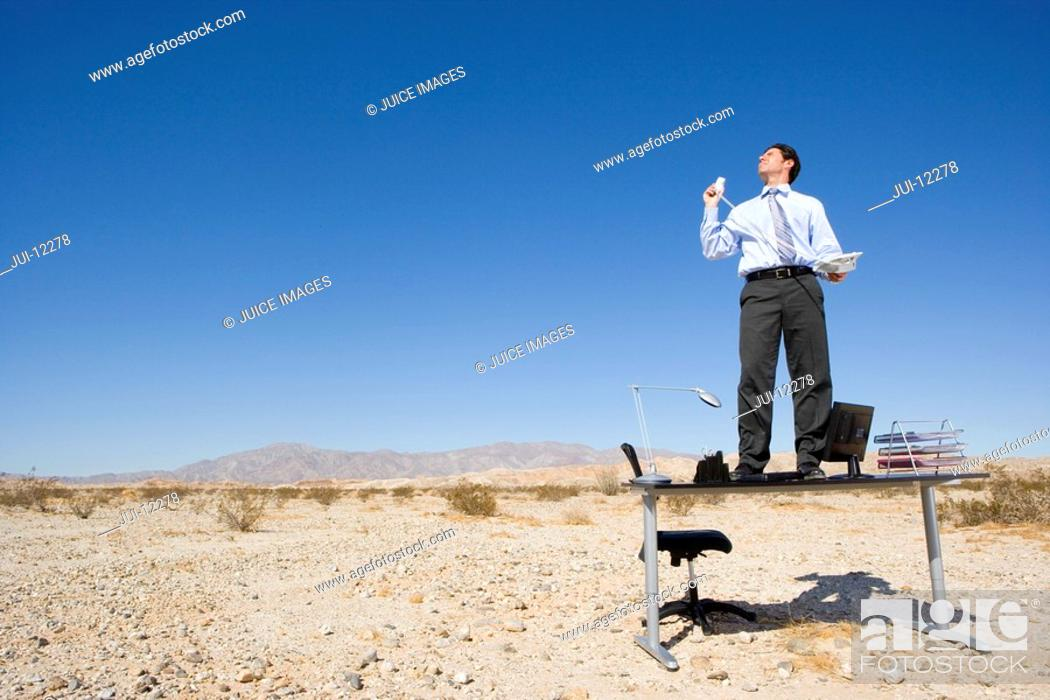 Stock Photo: Businessman standing on desk in desert, holding telephone and receiver, low angle view.