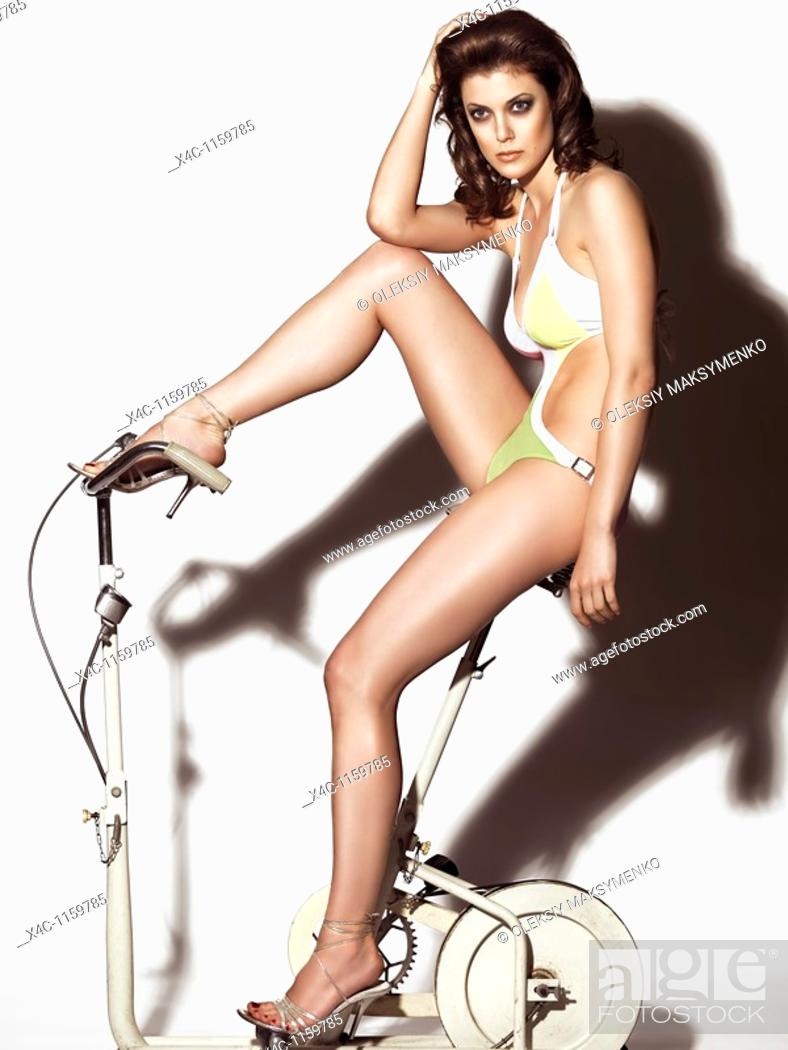 Stock Photo: Young woman in a trendy swimsuit posing on a retro exercise bike  Edgy high fashion photo.
