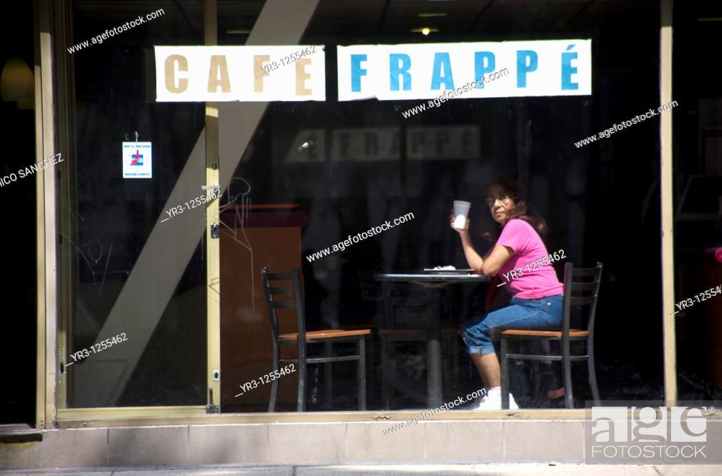 Stock Photo: A woman has a cup of coffee in a coffee shop in Paseo de la Reforma Avenue in Mexico City.