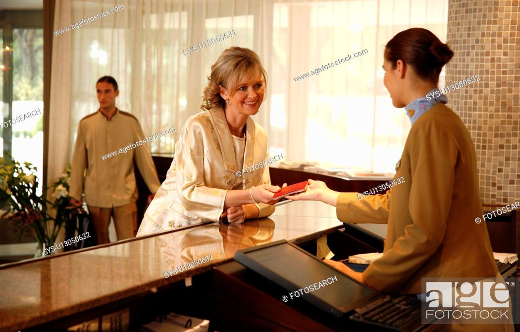 Stock Photo: Woman checking in at the hotel reception desk.