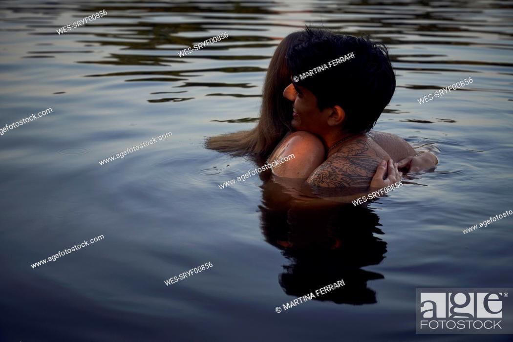 Stock Photo: Romantic couple embracing in lake at sunset.