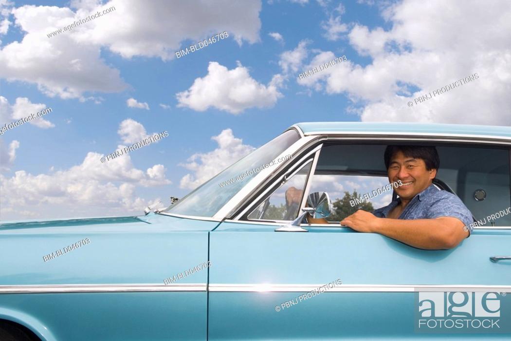 Stock Photo: Asian man sitting in car.