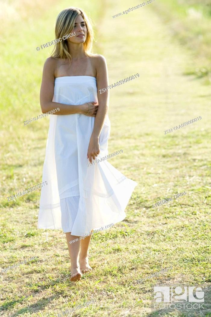 Stock Photo: Young woman walking across grass, full length.