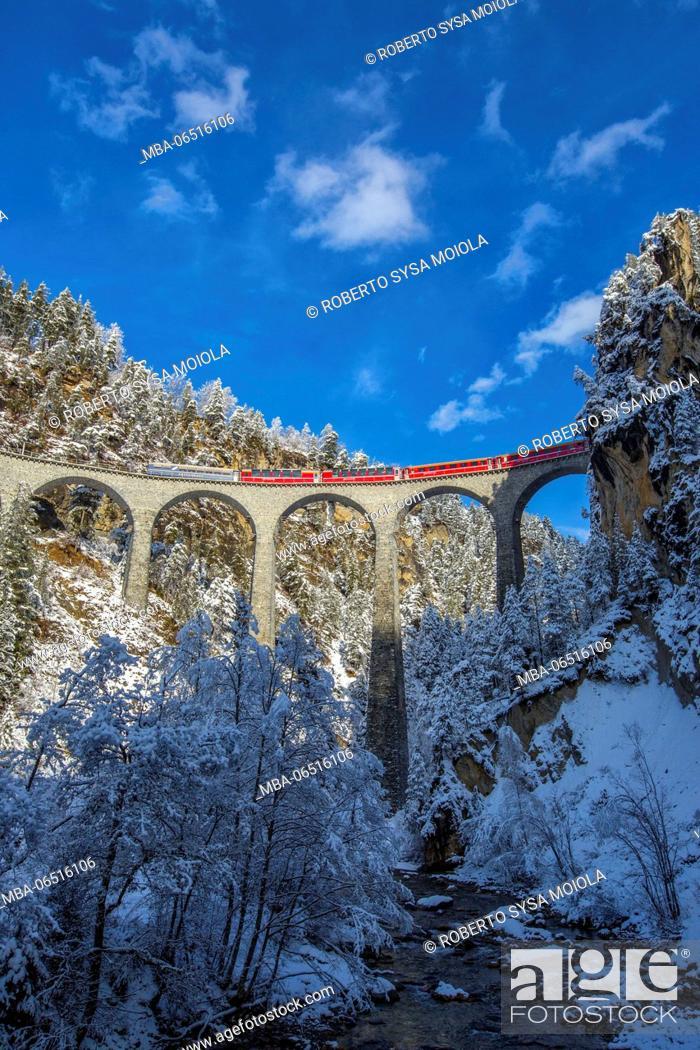 Stock Photo: Bernina Express passes through the snowy woods around Filisur Canton of Grisons Switzerland Europe.