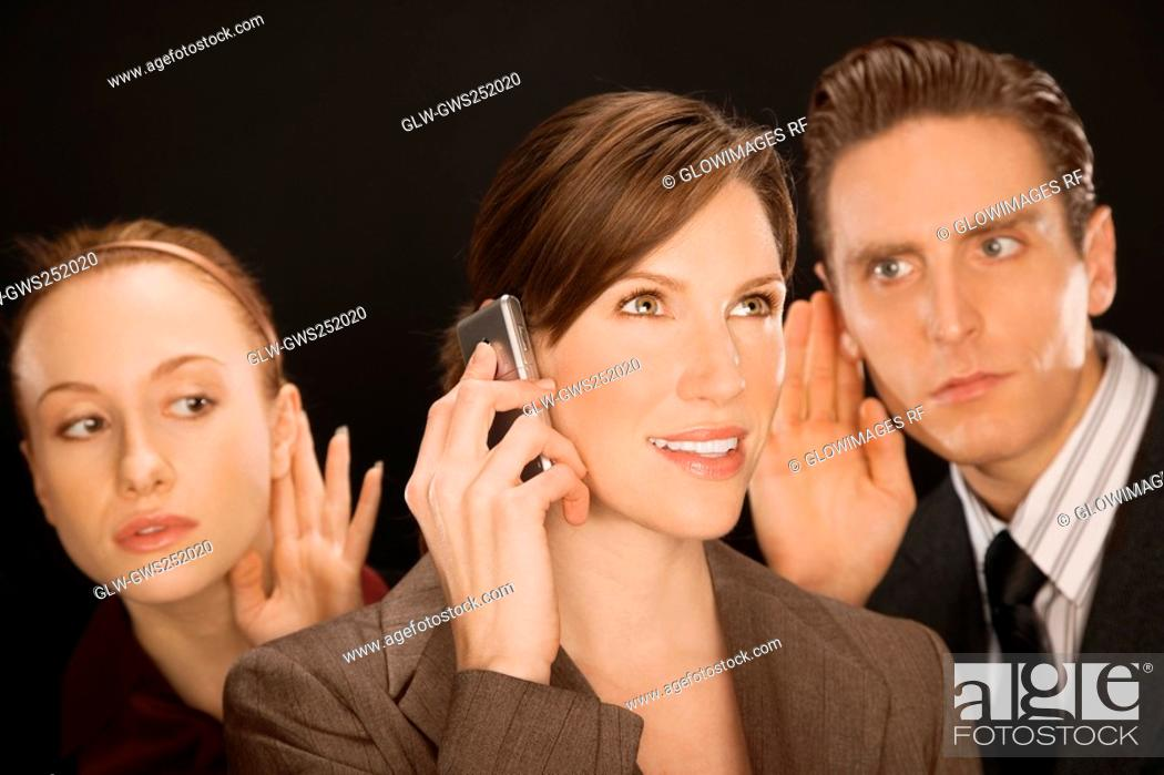 Stock Photo: Businesswoman talking on a mobile phone with two business executives listening to her.