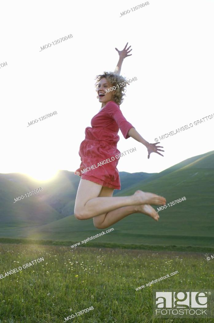 Stock Photo: Woman jumping for joy in mountain meadow side view.