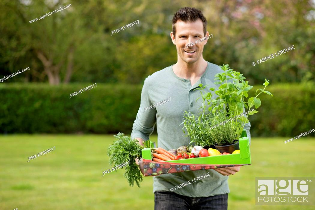 Stock Photo: Man holding a tray of raw vegetables.
