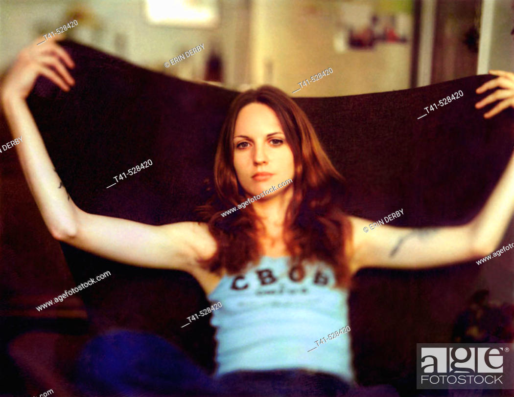 Stock Photo: A young woman rests in a brown chair in a small NY apartment. She wears a CBGB's tank top and has many tatoos.