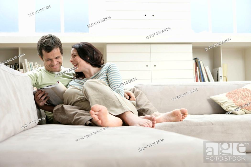 Stock Photo: Mid adult couple reading magazine on sofa.