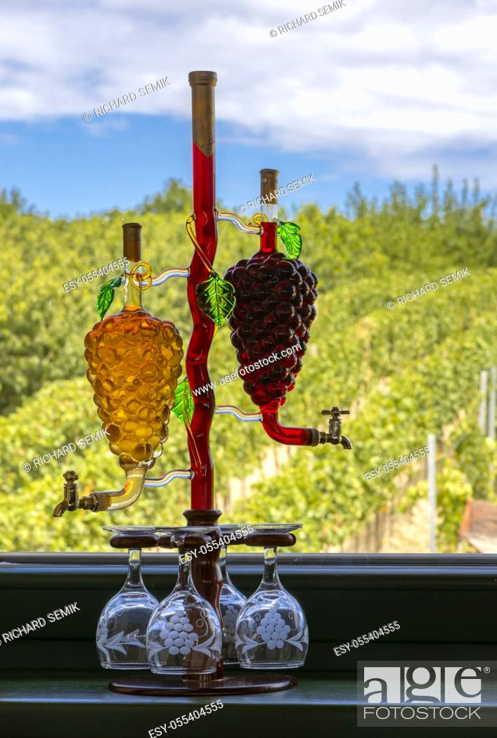 Stock Photo: glass carafe with white and red wine in the shape of a grape and vineyard background.