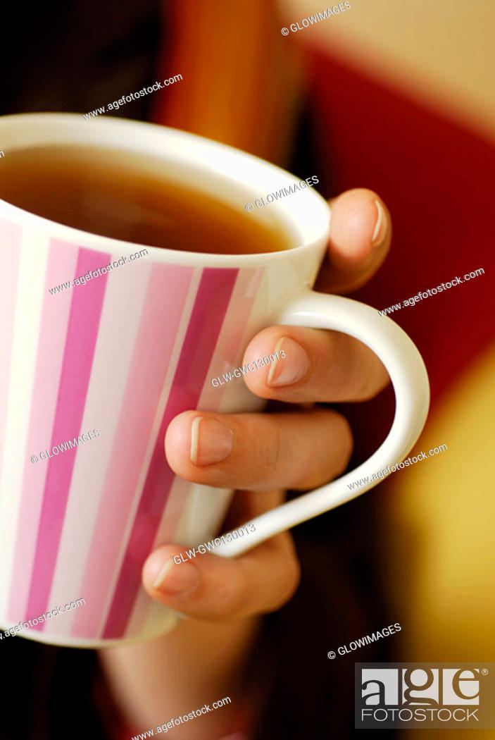 Stock Photo: Close-up of a person's hand holding a cup of black tea.
