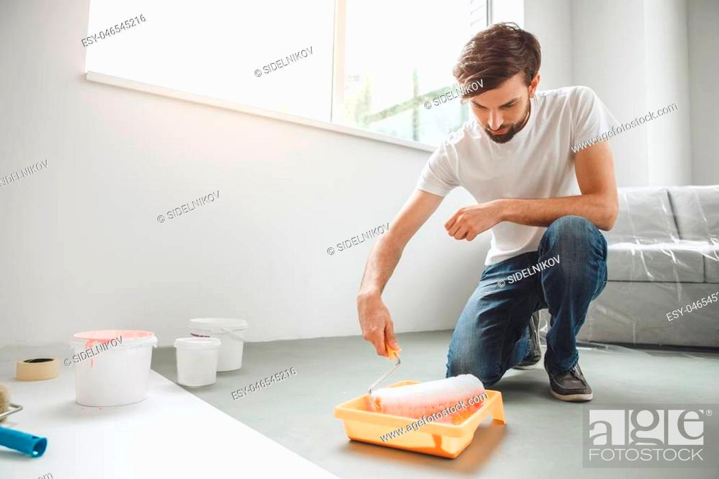 Stock Photo: Young male does apartment repairment himself painter.