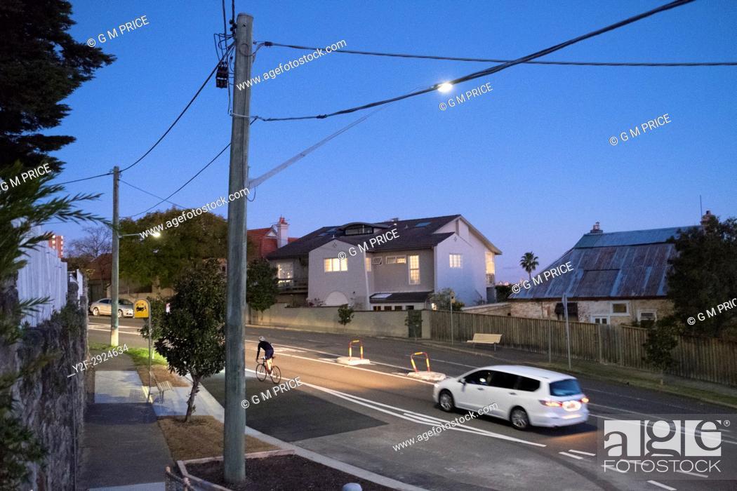 Stock Photo: car follows cyclist on hilly suburban street at dusk, Sydney.
