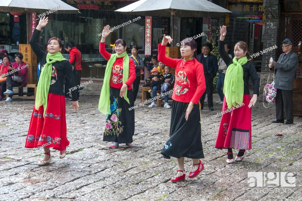 Stock Photo: Female folk dancers perform in a town square in the Old Quarter of Lijiang, Yunnan, China.