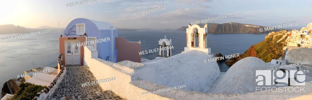 Stock Photo: Greece, View of Oia village in warm morning light with cobbled path at Santorini.