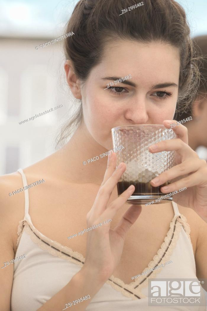 Stock Photo: Young girl holding a glass with a cool drink. Benicasim, Spain.