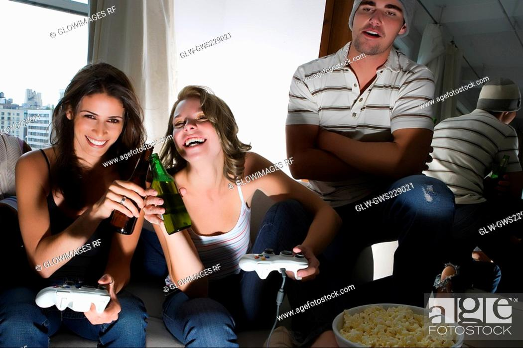Stock Photo: Two young women toasting with beer bottles and a young man standing beside them.