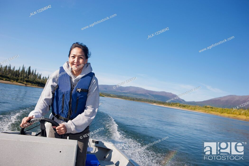 Stock Photo: Alaskan Native female driving a motor boat on Kobuk river, Arctic Alaska, summer.