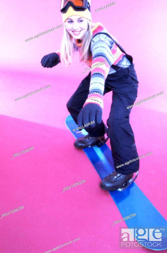 Stock Photo: Teenage girl (17-20) standing on a snowboard (toned).