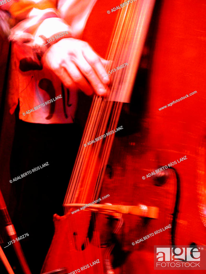 Stock Photo: A Jazz Musician Plays Bass In A Red Atmosphere. Chicago.