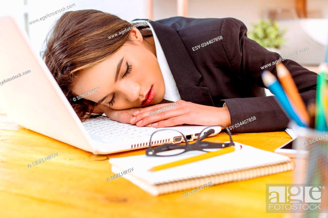 Stock Photo: Beautiful young business woman in modern office. Tired woman sleeping on laptop while working day.