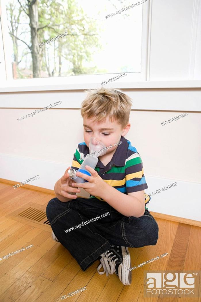 Stock Photo: Boy using asthma inhaler with spacer.