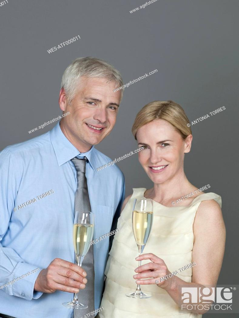 Stock Photo: Mature couple drinking sparkling wine, smiling, portrait.